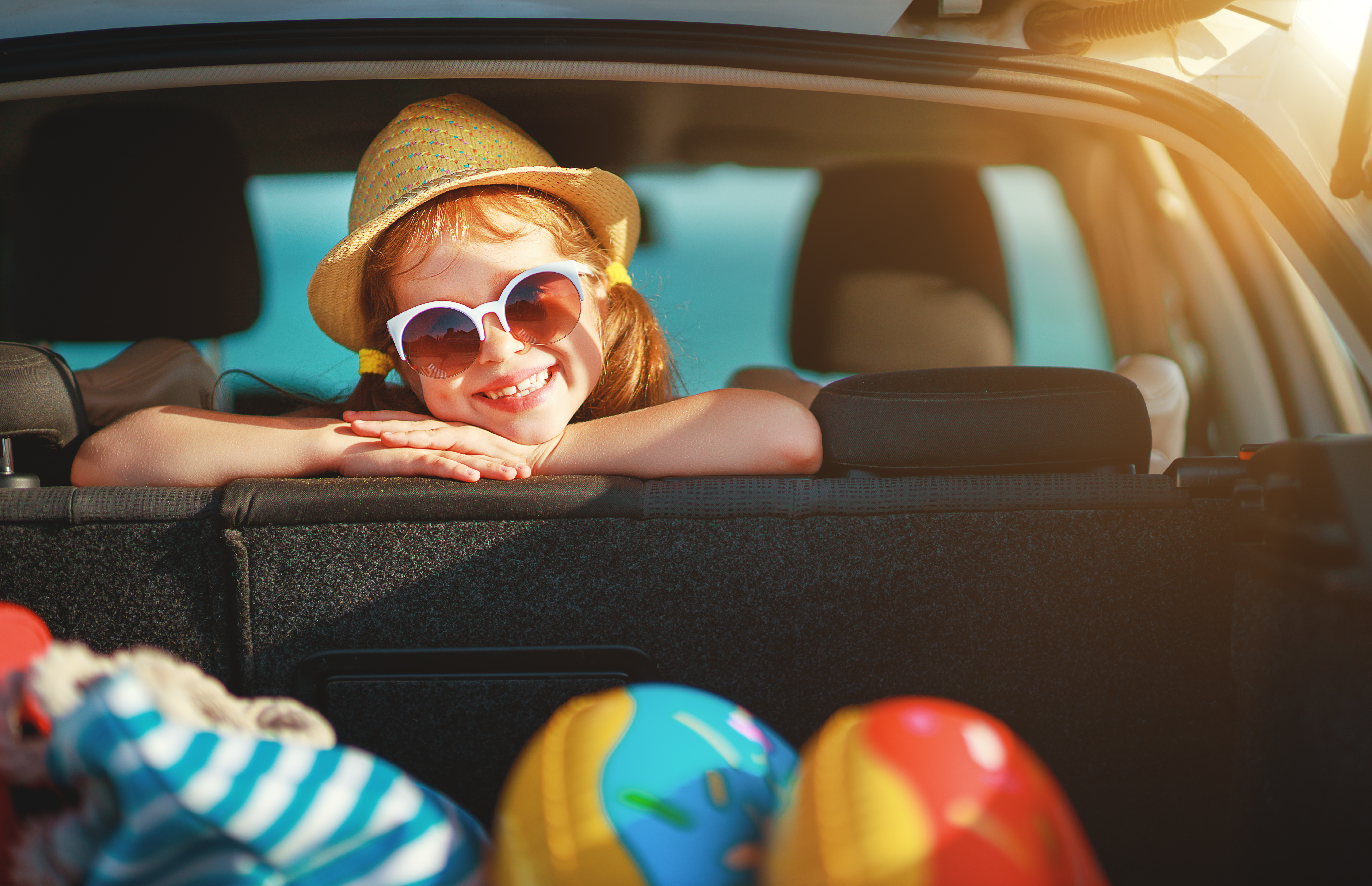 Young child in looking over backseat of car