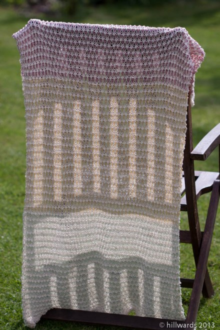 Cotton tricolour baby blanket draped on garden chair
