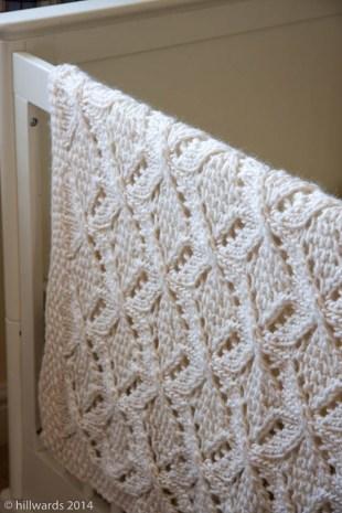 Umaro baby blanket hanging over cot
