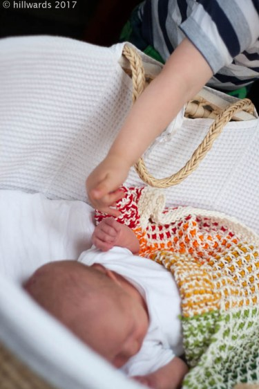 handmade knitted cotton baby blanket in rainbow stripes in use; baby and big brother