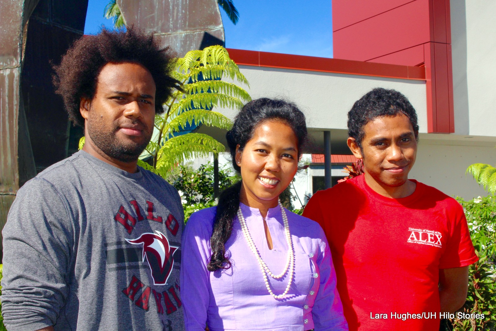 Student speakers at the UH Hilo International Film Festival (l-r)Peter Ramofolo in gray long sleeve shirt, Nandar Mya Yee in purple, and Helio Miguel Arcanjo Oliveira de Araujo. in red. The photo is taken outside with ferns and red building in the background.