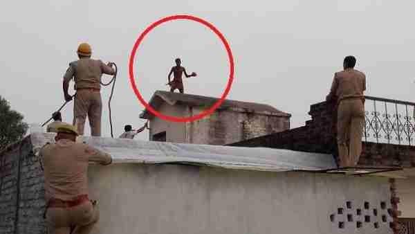 चार मंजिला मकान की छत पर चढ़ा शख्स