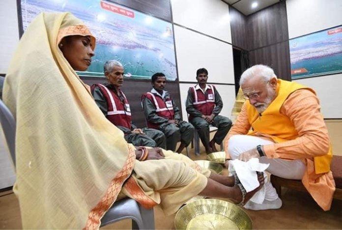 स्वच्छता दूतों के पाँव धोते हुए प्रधानमंत्री मोदी
