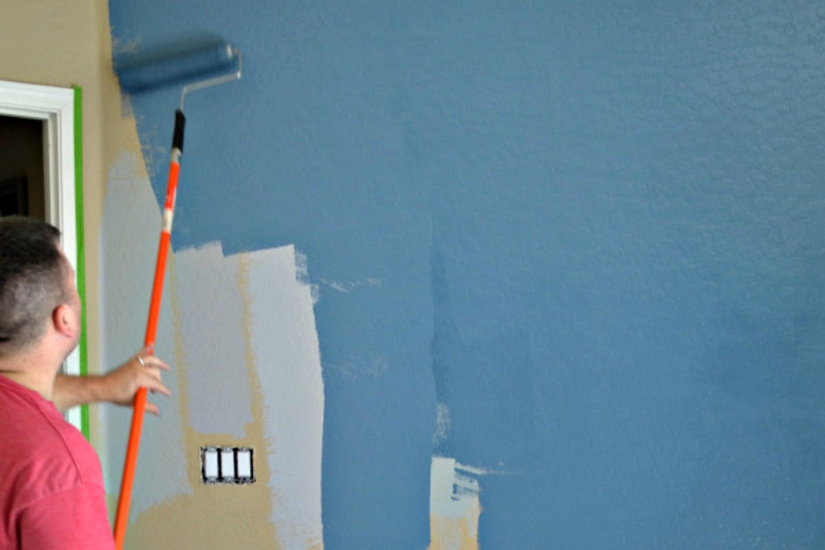 rolling blue paint onto a yellow wall
