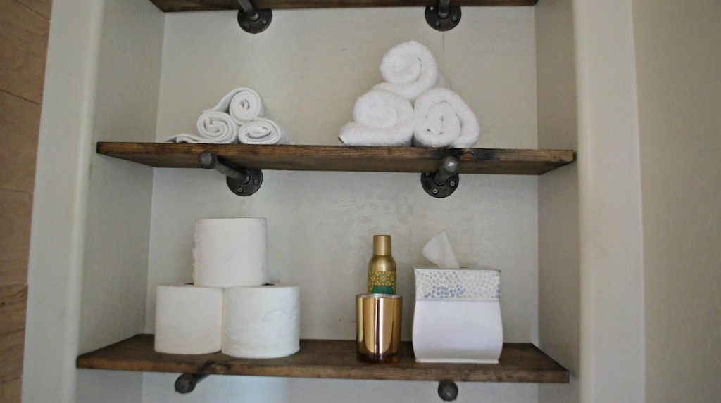 two brown and black wood shelves with toilet paper white towels and tissues