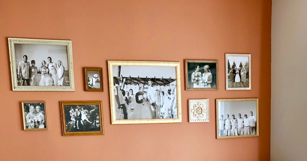 orange gallery wall with various sizes of picture frames