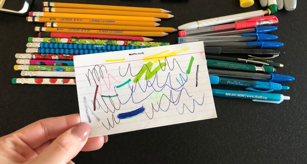 various colors of scribbles on paper with pens and pencils in the background
