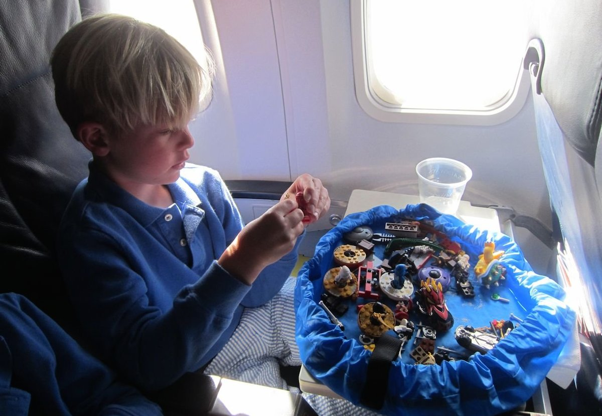 boy playing with toys on airplane with drawstring lay n go playmat