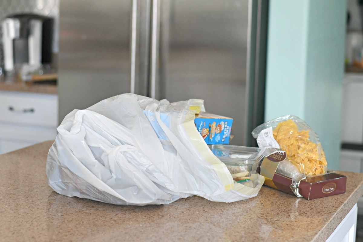 a plastic grocery sack with groceries on a counter
