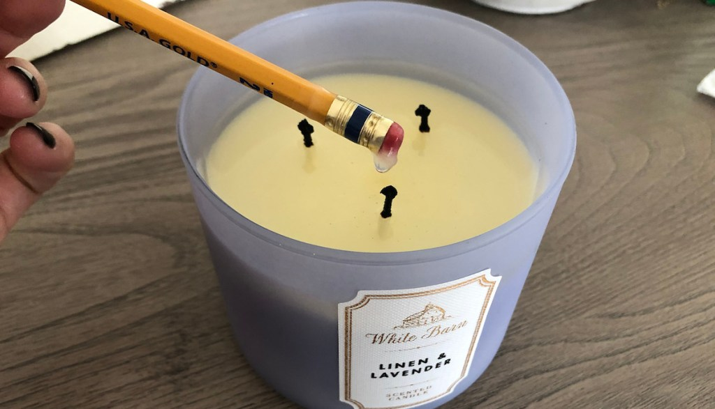 linen and lavender scented candle with melted wax and pencil dipped in wax