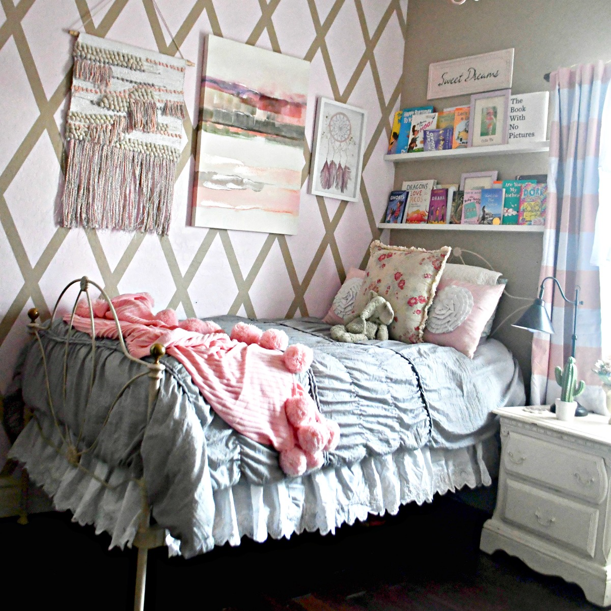 boho room with various decor and gray bedding with pink throw blanket