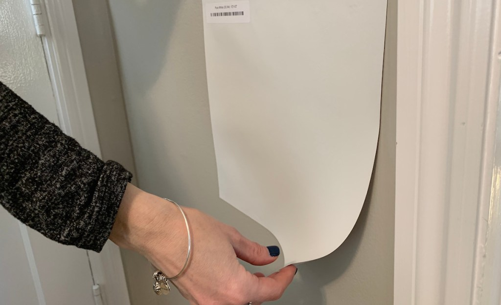 collins hand peeling off a white square paint sample on a gray wall