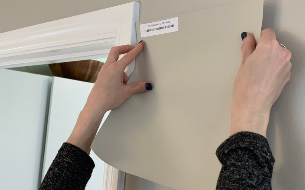 two hands holding a revere pewter paint sample on gray wall with white trim