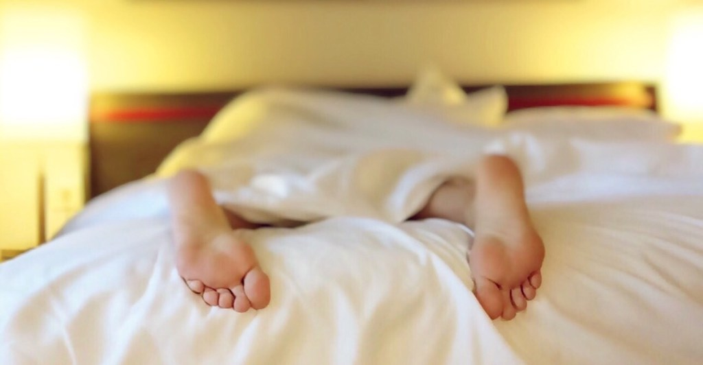 pair of feet hanging off white bed with bright yellow lights in background