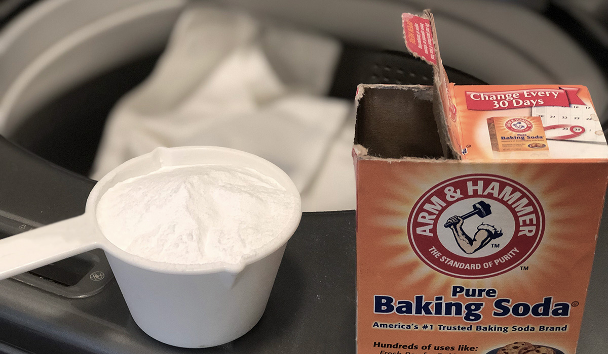 a measuring cup of baking soda next to a washing machine