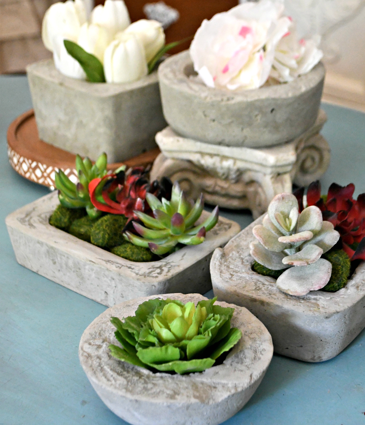 tabletop with a collection of concrete planters styled with flowers and succulents