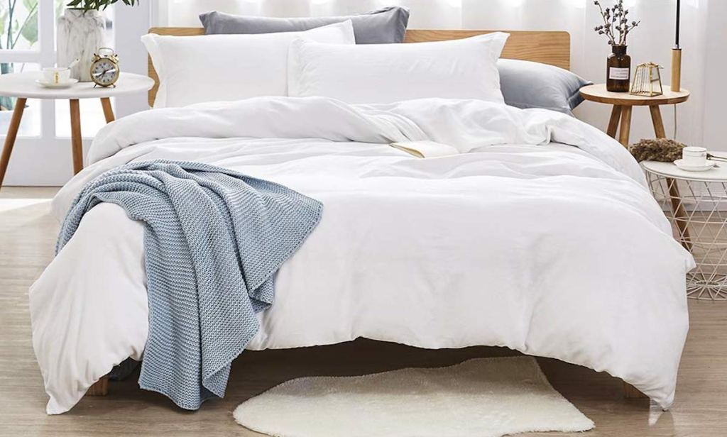 white bedding with pillows and blue throw with small white rug on floor