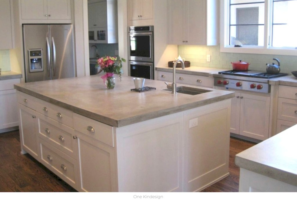 white kitchen cabinets with cement countertops with stainless steel appliances