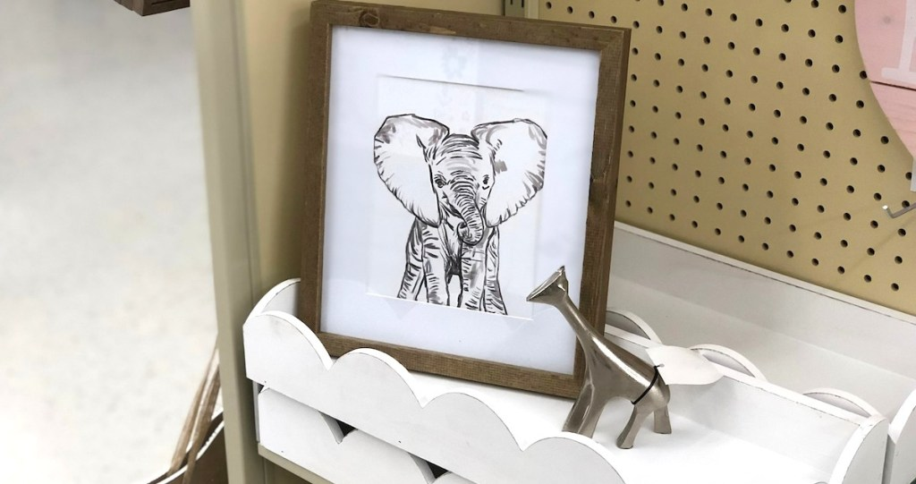elephant picture sitting on white scalloped shelf with silver metal giraffe