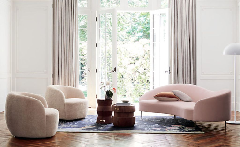 white chairs and pink sofa in a mid century modern and chic living area