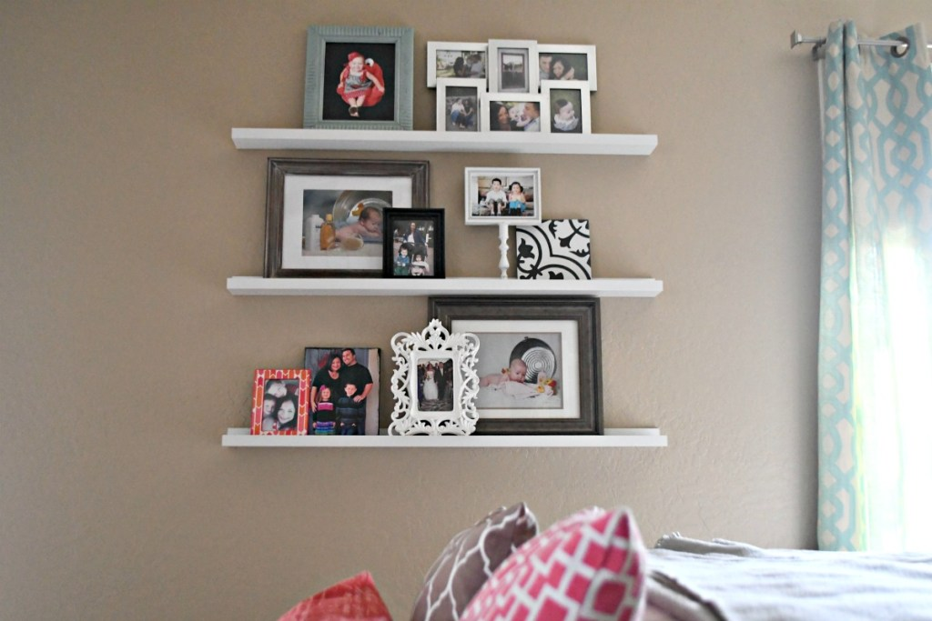 photos displayed on Ikea picture ledges as a gallery wall