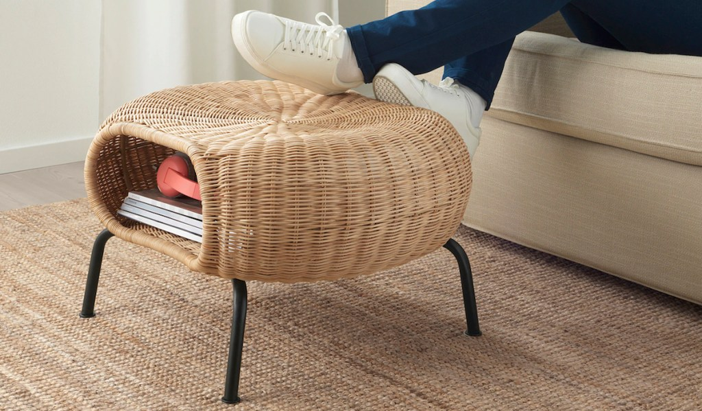 feet resting on round wicker ottoman with black legs and books inside