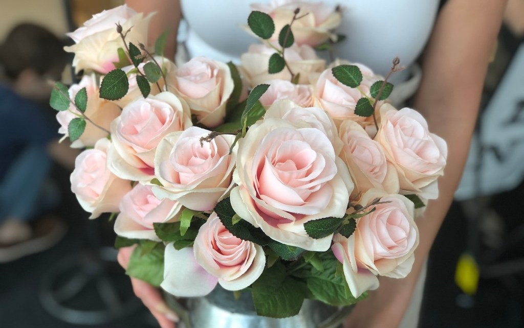 tons of pink roses in a metal jar
