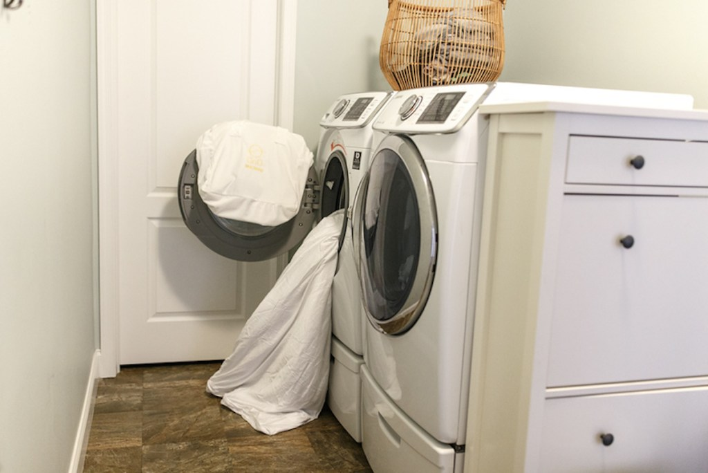 white front loading washing machine with white blanket cascading out