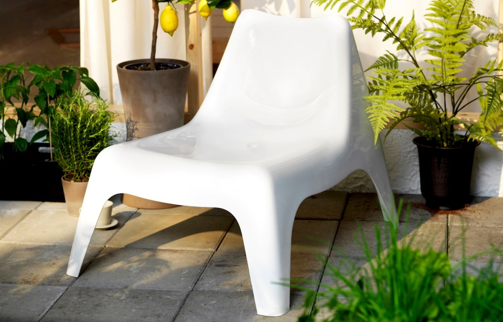 modern white plastic chair sitting outside with lemon tree hanging over it