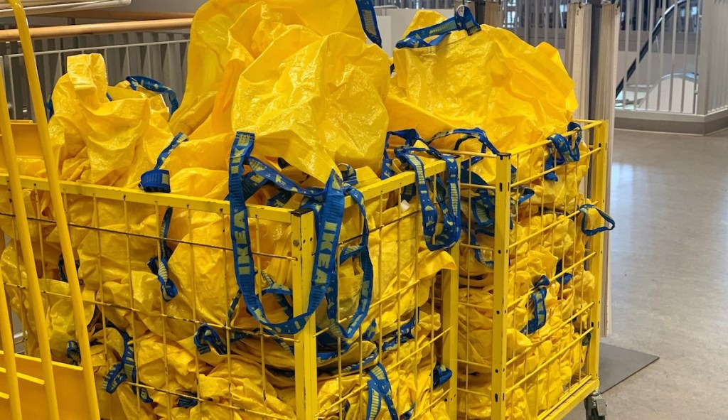 yellow reusable ikea bags with blue handles sitting in a large yellow bin
