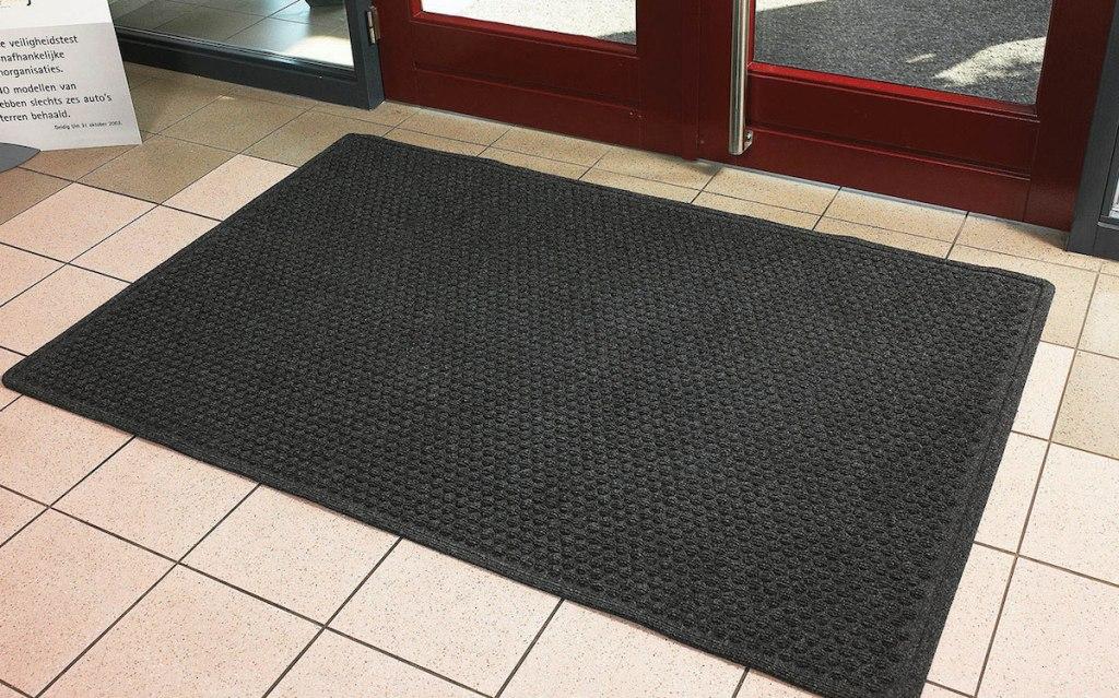 black door mat sitting on beige tile floor