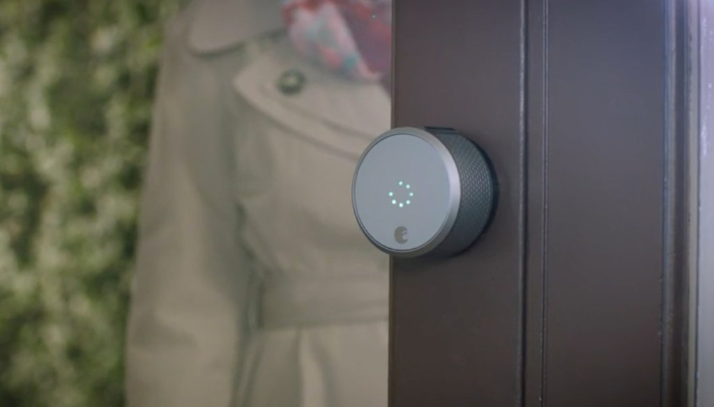 glass door with round device on edge of door with person in trench coat in the background