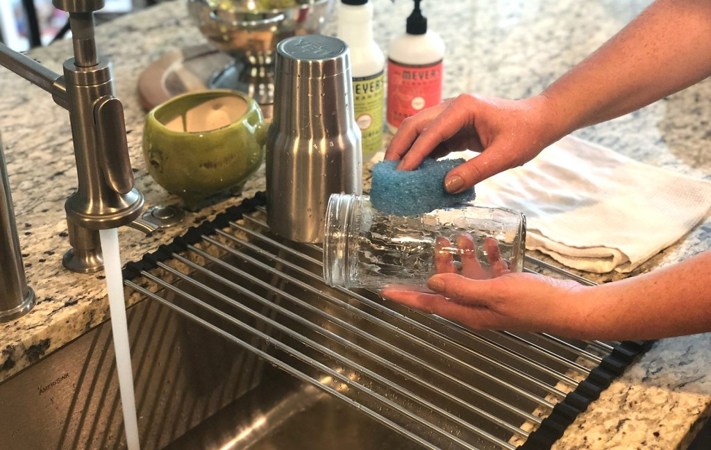 hand washing a clear glass cup with running sink water
