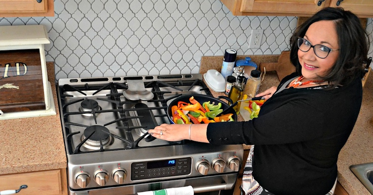 woman cooking colorful vegetables on gas stainless steel cooktop range