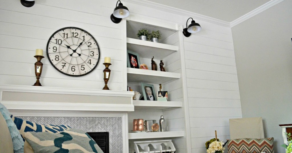 white shiplap wall with fireplace three black farmhouse barn lights and bookshelves