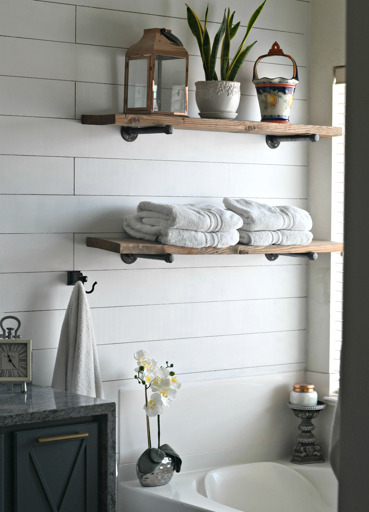 wood and pipe shelving above bath tub for towel storage