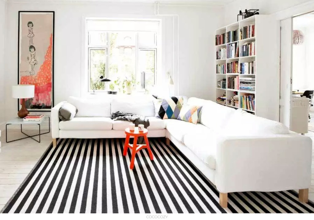 black and white stripe rug in living room with large white sectional couch and red stool and bookshelves