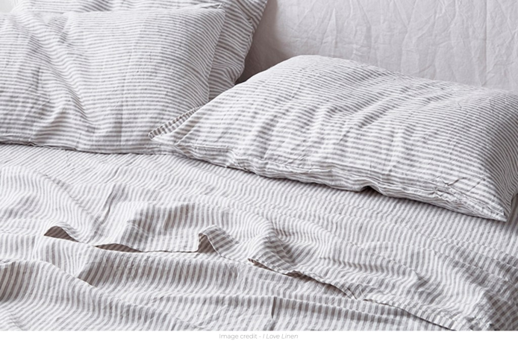 white and gray ticking stripe sheets on bed with pillows