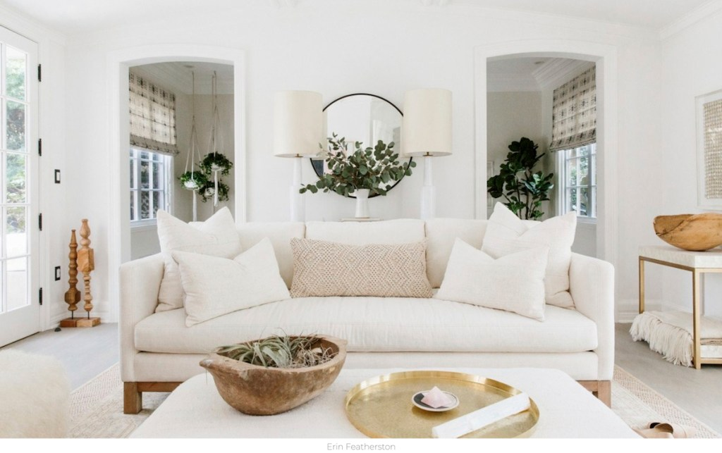 white living room with white walls beige couch soda with pillows and coffee table with decor
