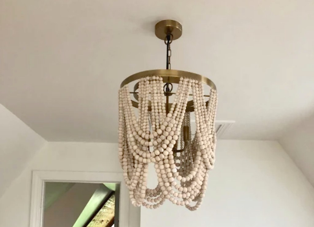 wood bead chandelier with gold accents hanging from white ceiling