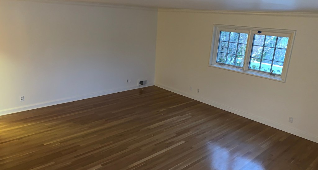 empty room with wood floors white walls and two small windows