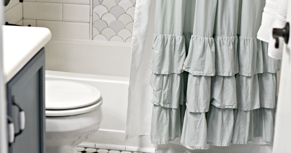 ruffle shower curtain with liner behind it in the bathroom