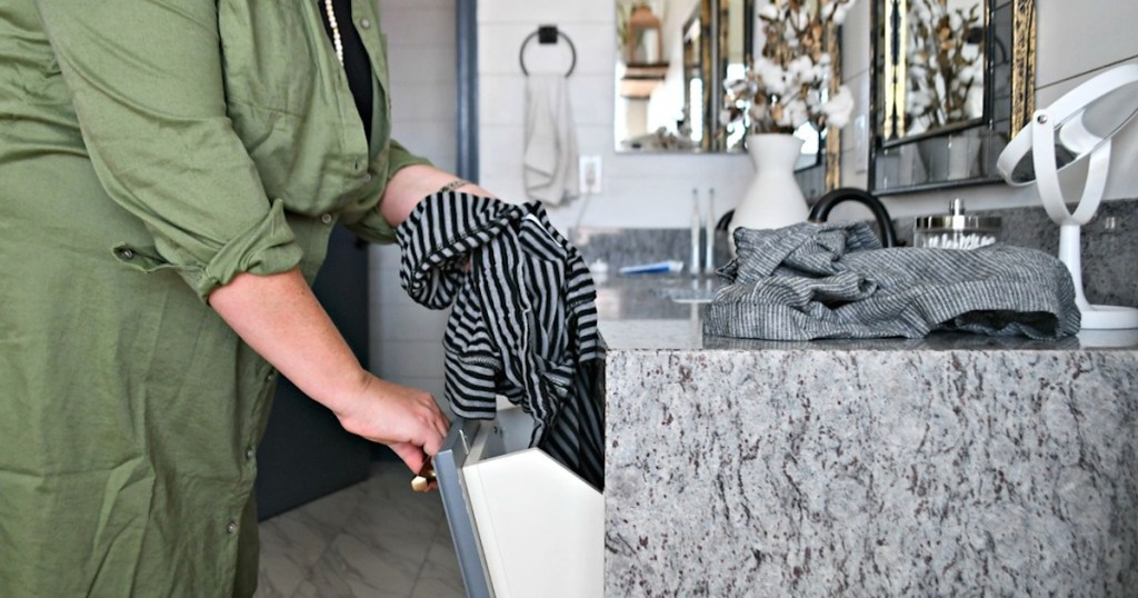 woman holding dirty clothes putting into laundry chute cabinet door in bathroom