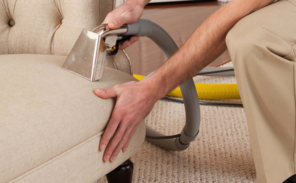 person steam cleaning beige tan couch sofa