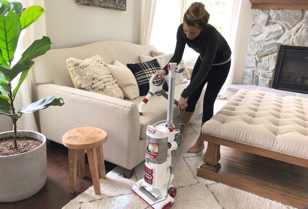 woman vacuuming couch living room