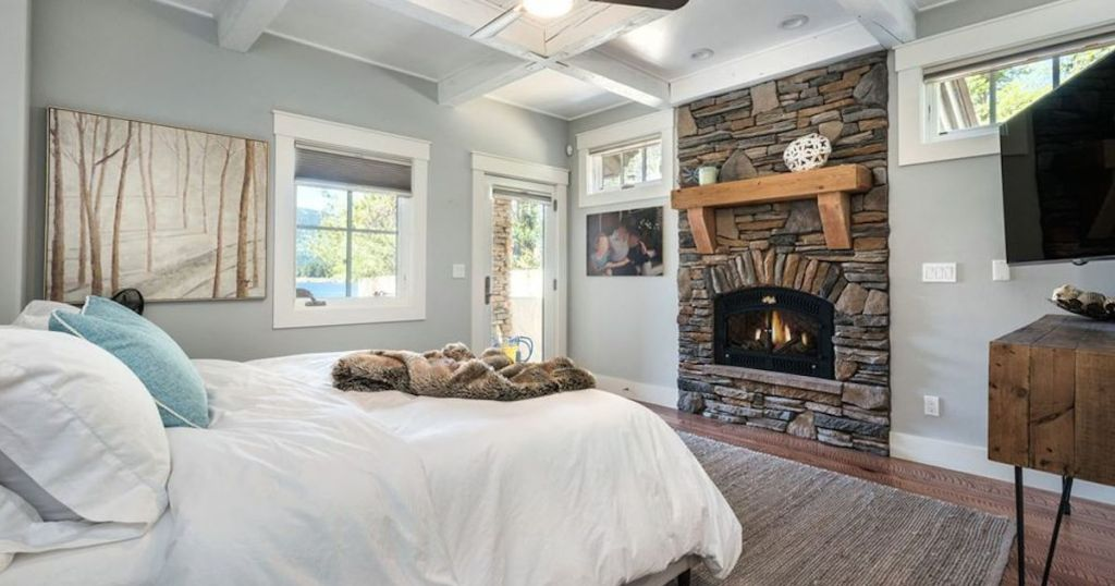 blue room with white bed and stone fireplace