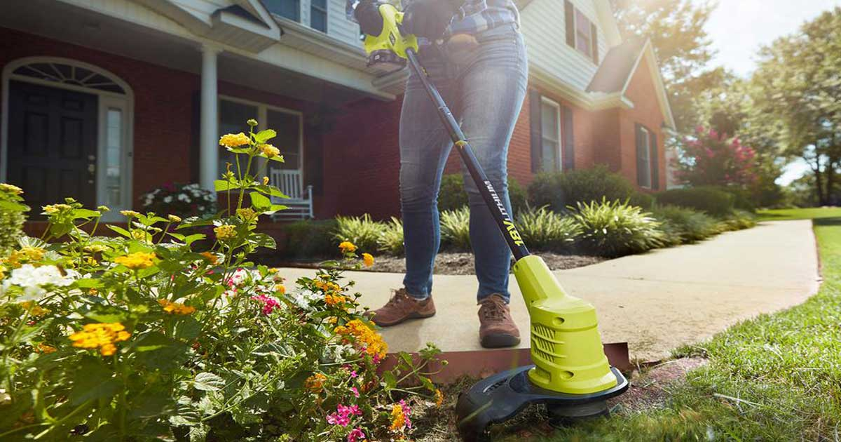 person using a lawn trimmer on a yard in front of a house