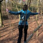 Woman wearing a harness crossing a rope bridge