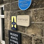 Blue plaque and Muddy boots welcome signs on side of pub