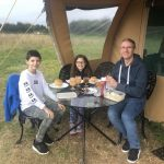 Family sit outside tent at a table eating